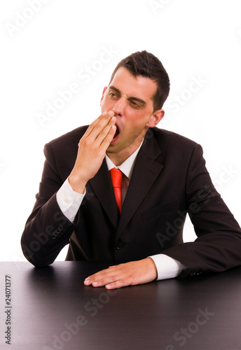 yawning young business man on the desk, on white background