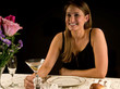 Young woman enjoying martini in restaurant or dining room
