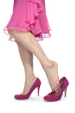 Woman legs with pink heels and dress over white