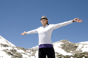 Female hiker with hands raised