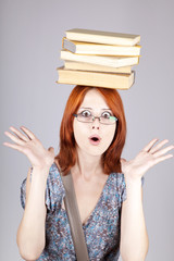 Red-haired girl keep books on her head. Studio shot.