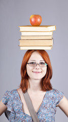 Red-haired girl keep apple and books on her head.