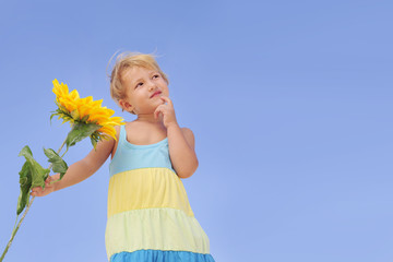 Cute child with sunflower looking at copy space