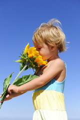 Cute child smelling a sunflower