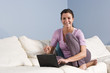 Woman sitting on couch at home with laptop