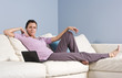 Woman reclining on couch at home with laptop
