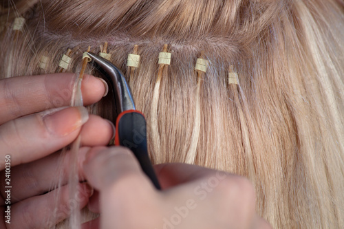 Stylist putting hair extension for a model
