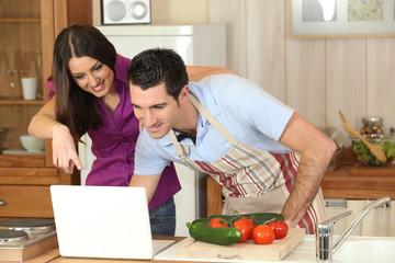 Couple devant un ordinateur dans la cuisine