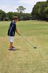 young boy driving a golf ball
