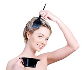 Woman with brush and capacity for hair-dye coloring her hair poster