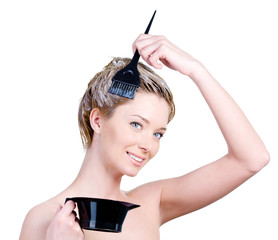 Woman with brush and capacity for hair-dye coloring her hair