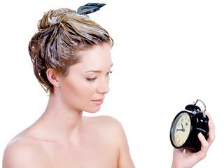 Woman coloring hair and looking at clock