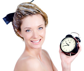 Woman with smile coloring hair holding alarm