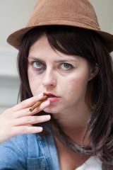 Young junkie woman smoking a cigar