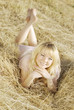 Young pretty girl in pink dress laying on haystack