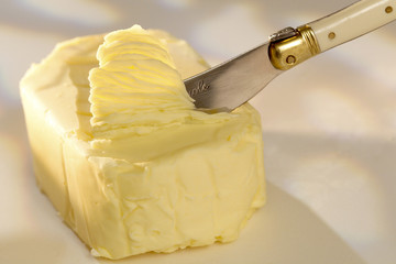 knife srapping the pat of butter
