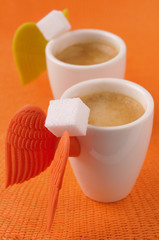 two cups of expresso and white sugar lumps