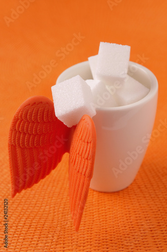 white sugar lumps in a china cup with wings