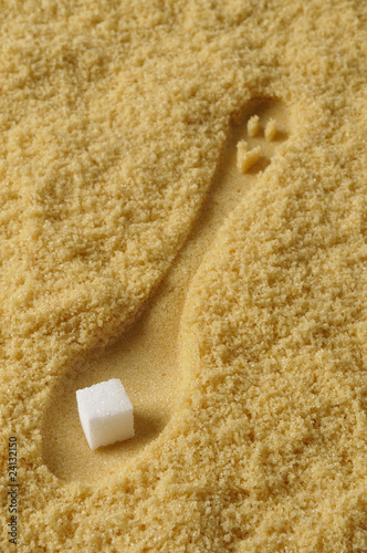 print of a spoon in brown sugar and a white sugar lump