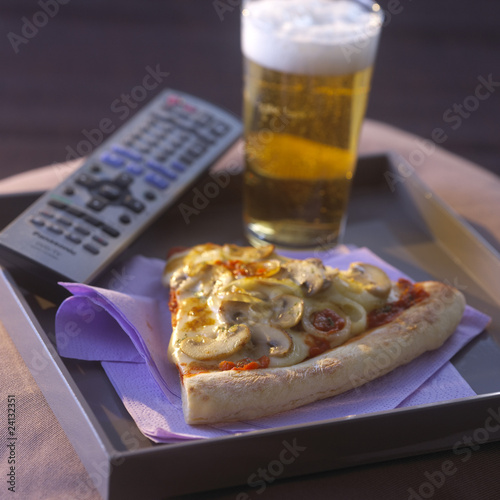 t.v dinner with a portion of pizza and a glass of beer