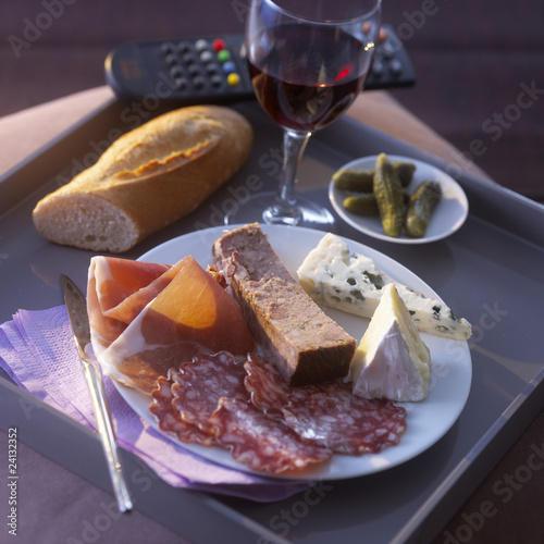 t.v dinner with a plate of cold cuts and cheese and a glass of red wine
