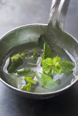 fresh mint in a ladle of water