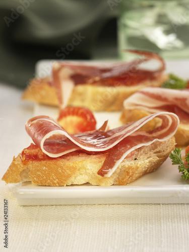 spanish ham and tomato on a bite-size slice of bread
