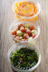 lebanese tabbouleh,tomatoes and mozzarella,grated carrots in plastic containers