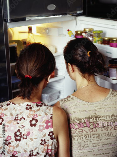 girls looking in a refrigerator
