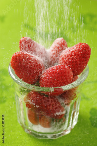 powdering strawberries with sugar