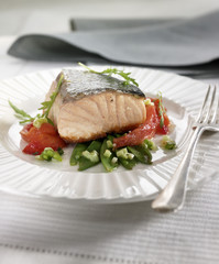 thick piece of salmon with tomatoes
