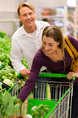 Leute im Supermarkt kaufen Gemüse