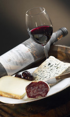 plate of cheese and dried sausage,bottle and glass of red wine