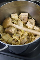 adding the tripe cubes to the onions in the stewpot