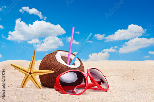 A coconut, starfish and a sunglasses on a beach
