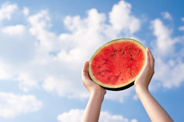Wassermelone vor wolkigem, blauem Himmel