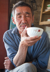 The adult person the native of Asia  drinks tea from a cup