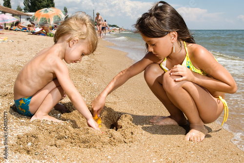 Two young kids digging sand at the beach