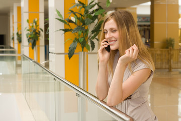 young attractive woman speaking on cellphone in shopping centre