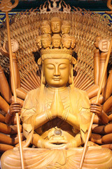 The big kuan has thousand hands. Statue from woods.