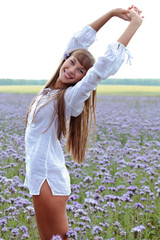 Portrait of a beautiful woman on a green meadow with hands up