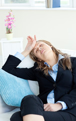 Stressed businesswoman slepping on a sofa