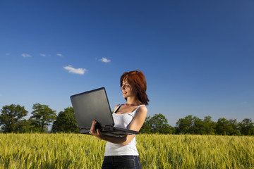 Young agronomist in the wheat field working with laptop