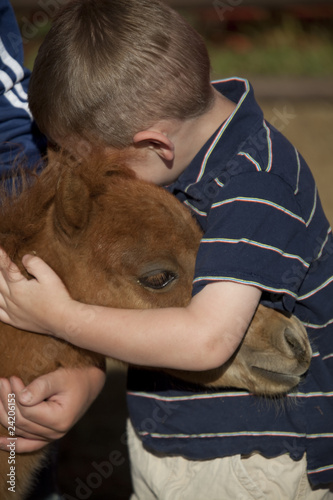young boy hugging horse