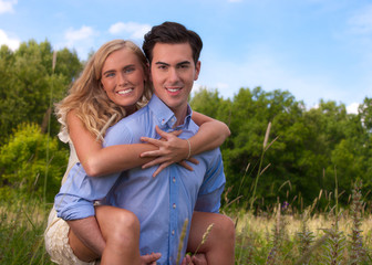 Beautiful, young couple piggybacking in tall Summer grass