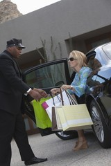 Chauffeur helps woman from luxury vehicle