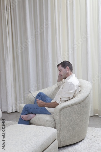 Man sits reading a digital book