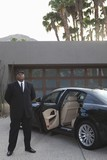 Chauffeur stands at open car door of luxury vehicle