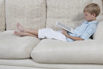 Boys sits on sofa reading a digital book