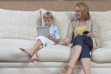 Mother and son sit on sofa, boy with digital book
